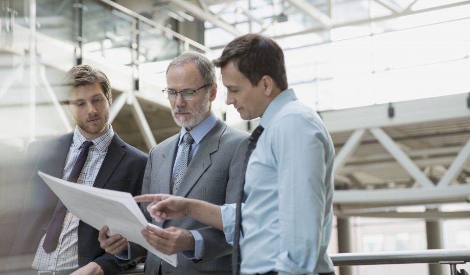 Businessmen discussing paperwork in meeting