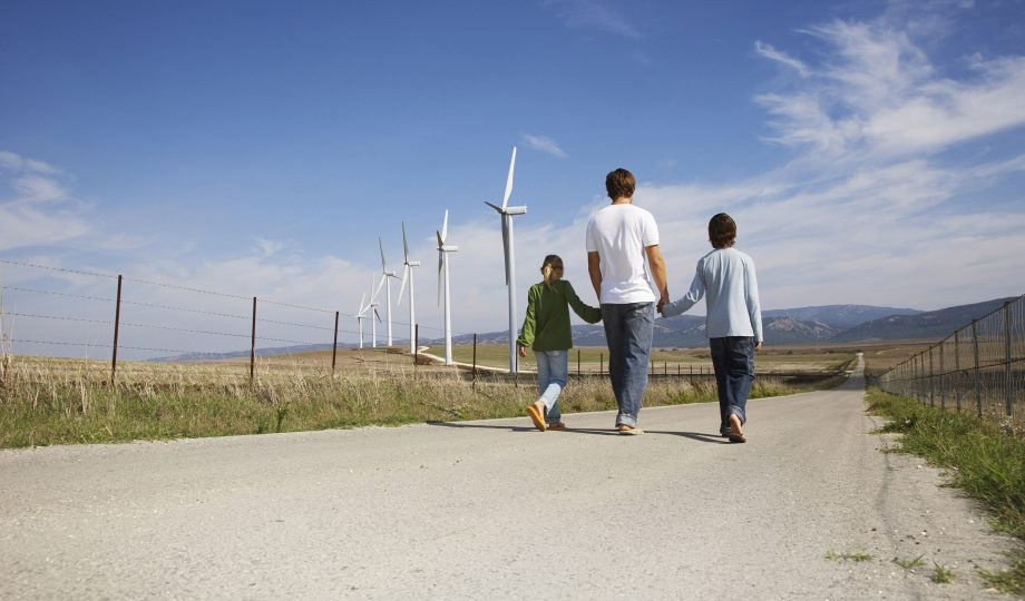 Why Evergreen, Father and Children Walking on Rural Road, next to Wind Turbines