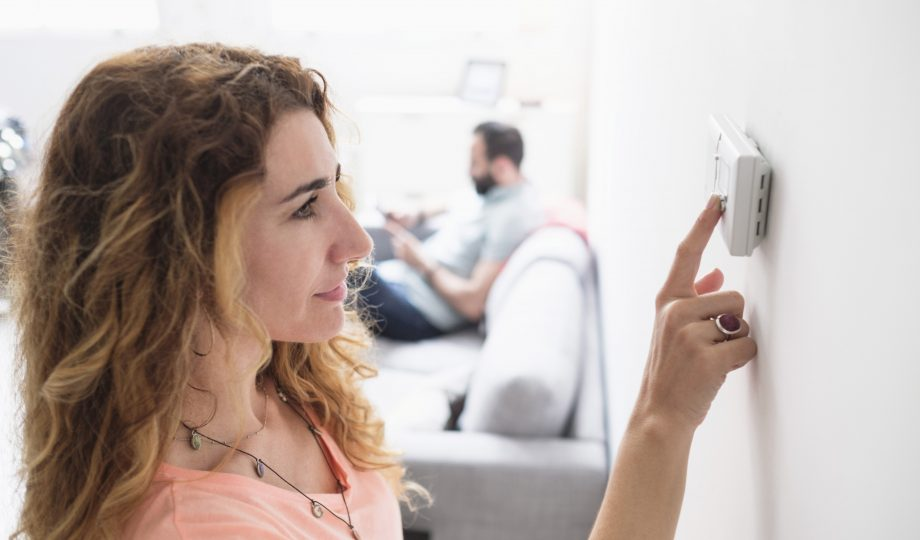 woman adjusting thermostat to save energy