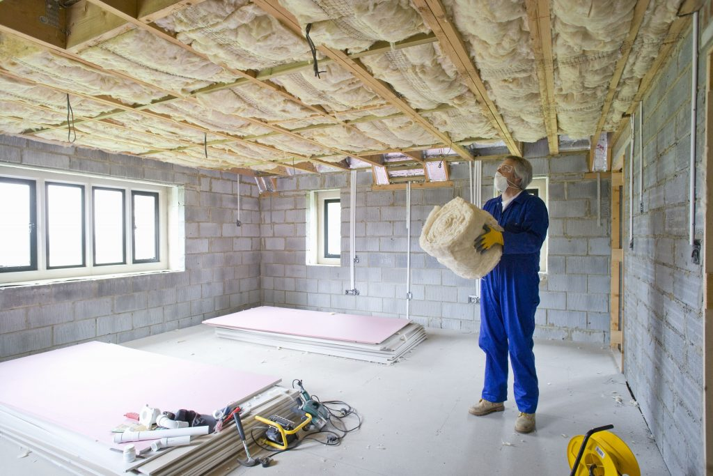 Man holding ceiling insulation in house under construction